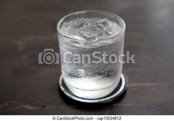 Glass with water on wood background - csp10534812