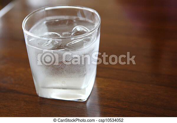 Glass with water on wood background - csp10534052