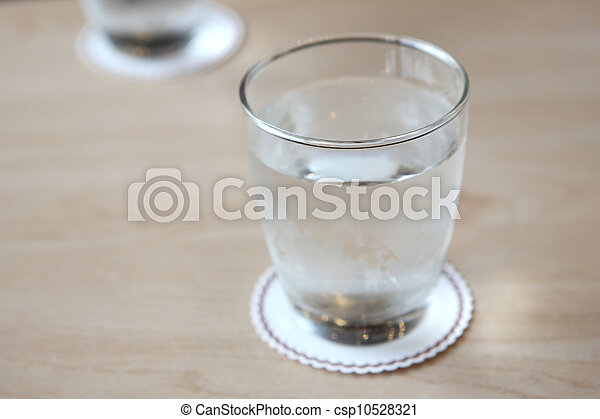 Glass with water on wood background - csp10528321