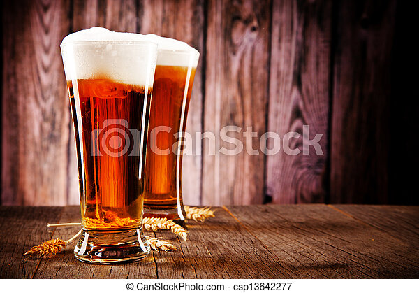 Glasses of beer on wooden table - csp13642277