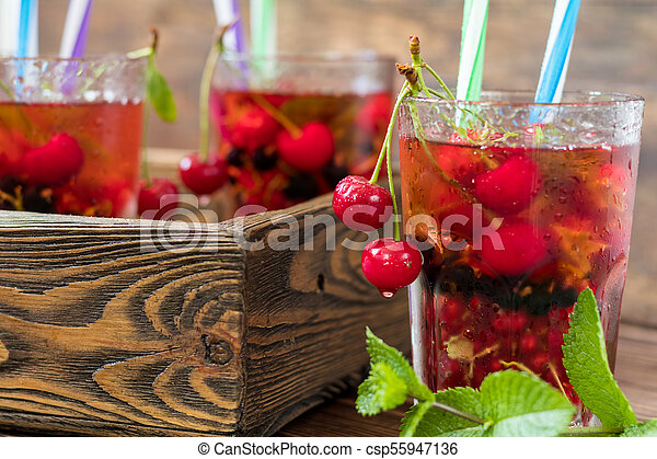 Glasses of refreshing drink flavored with fresh fruit and decorated with cherries covered with dew drops - csp55947136