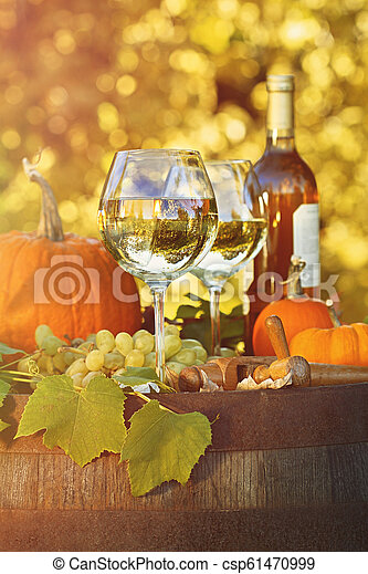 Glasses of white wine with pumpkins on barrel - csp61470999