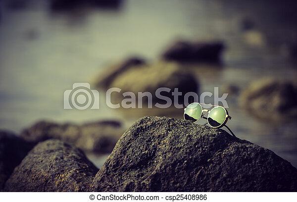 Glasses on the rock near the sea - csp25408986