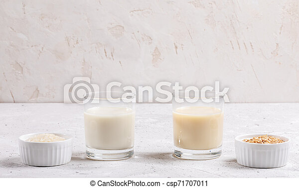 Glasses with healthy rice and oat milk, bowls with rice seeds and oat flakes on white background. - csp71707011