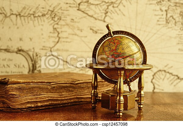 Globe and vintage book against map on a wall. - csp12457098