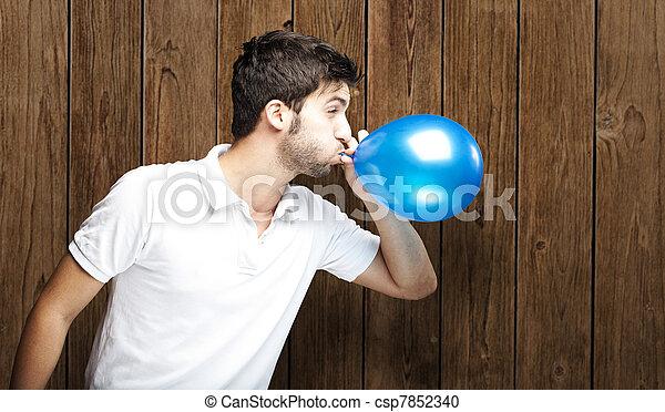 Hombre soplando globo - csp7852340