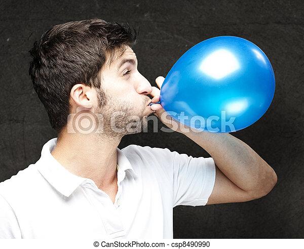 Hombre soplando globo - csp8490990