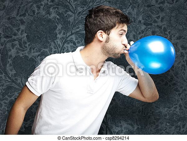 Hombre soplando globo - csp8294214