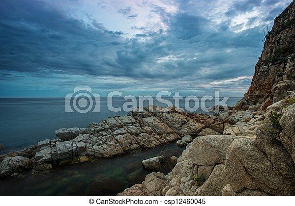 Gloomy sky over rocky shore - csp12460045