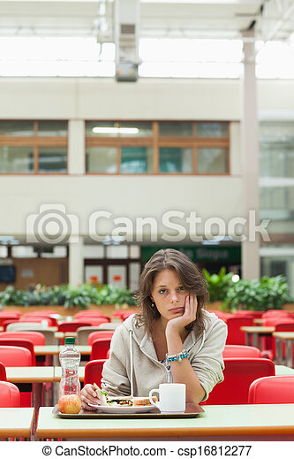 Gloomy student in the cafeteria with food tray - csp16812277