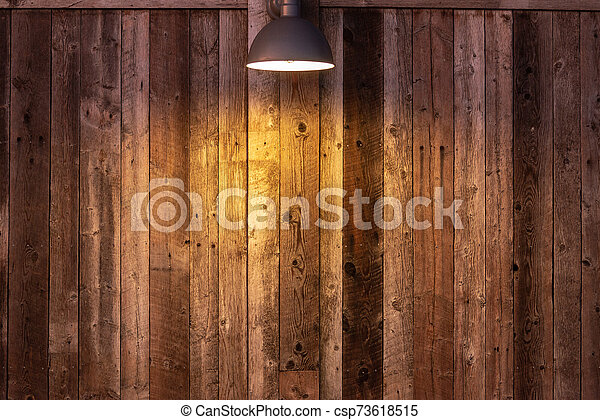 Glowing light bulb on wooden background. Light falling from old vintage lamp on wall. - csp73618515