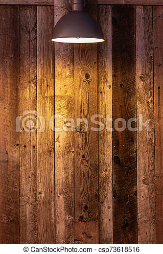 Glowing light bulb on wooden background. Light falling from old vintage lamp on wall. - csp73618516