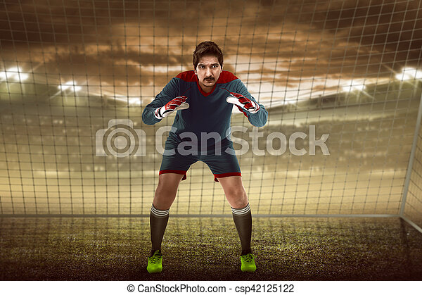 Goalkeeper in front of goalpost - csp42125122