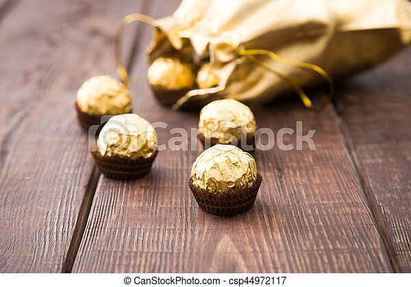 gold bag of chocolates. candy in Golden foil with copy space - csp44972117