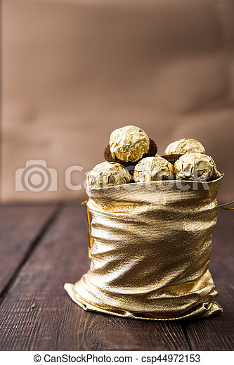 gold bag of chocolates. candy in Golden foil with copy space - csp44972153
