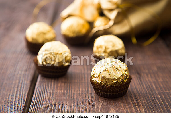 gold bag of chocolates. candy in Golden foil with copy space - csp44972129