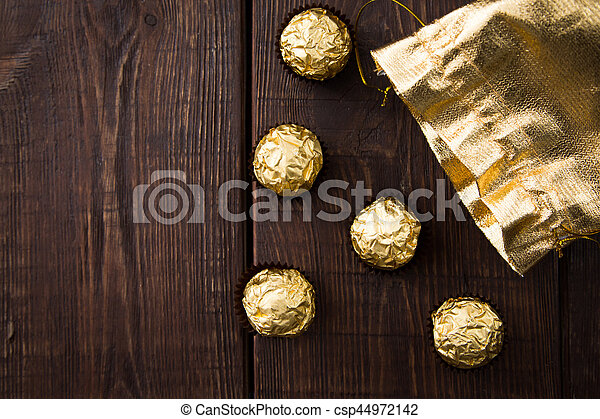 gold bag of chocolates. candy in Golden foil with copy space - csp44972142