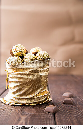 gold bag of chocolates. candy in Golden foil with copy space - csp44972244