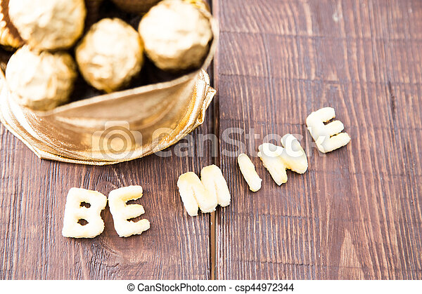gold bag of chocolates. candy in Golden foil with copy space - csp44972344