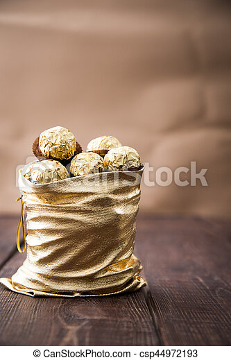 gold bag of chocolates. candy in Golden foil with copy space - csp44972193