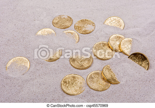 Gold coins on a grey sand - csp45570969