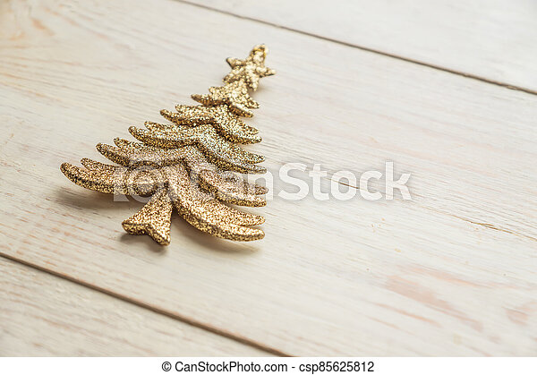 Gold decorative christmas tree toy  on wooden background. Festive New Year winter concept - csp85625812