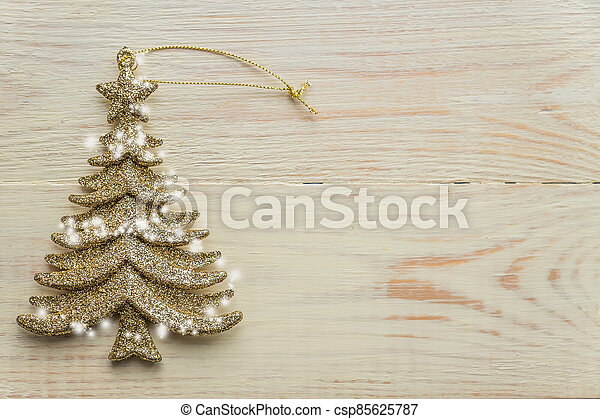 Gold decorative christmas tree toy  on wooden background. Festive New Year winter concept - csp85625787