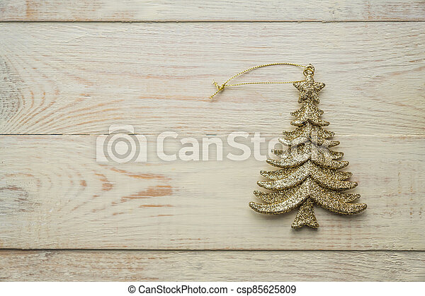 Gold decorative christmas tree toy  on wooden background. Festive New Year winter concept - csp85625809