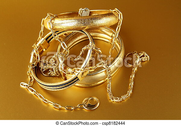 Gold jewelry bracelets and chains on gold background stock photo