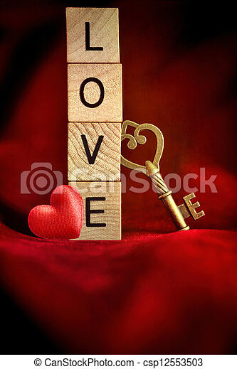 Gold key with wooden block letters that spell the word love - csp12553503