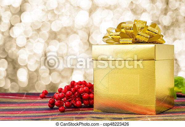 Gold present box with ribbon on table with sparkling gold bokeh light background, Leave space for adding your text - csp48223426