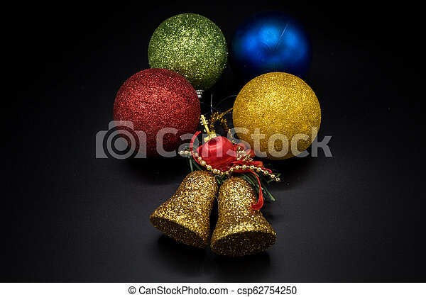 Golden Bell And Colorful Christmas Balls On Black Background