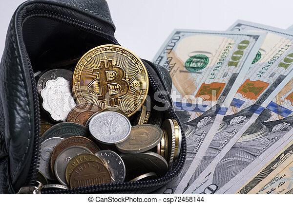 golden bitcoin coin over money coins in wallet around dollars. close up - csp72458144