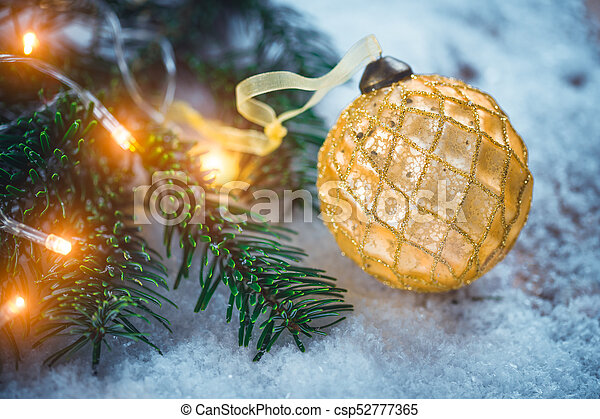 Golden Christmas ball with ribbon on snow near fir branch with bright garland. Festive background with copy space - csp52777365
