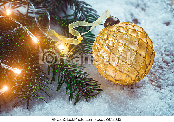 Golden Christmas ball with ribbon on snow near fir branch with bright garland. Festive background with copy space - csp52973033