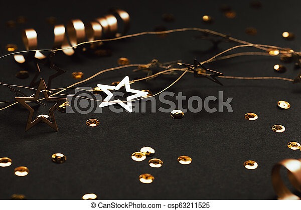 Golden decor of ribbons, confetti and star garland on black background. - csp63211525