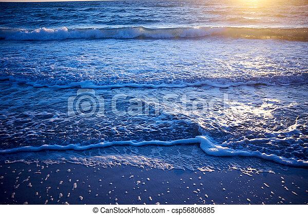 Golden glow of sunset over a calm ocean - csp56806885