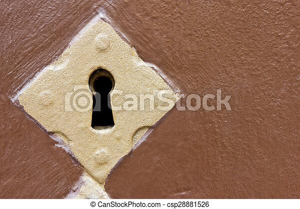 Golden keyhole in a brown door - csp28881526