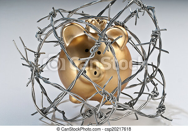 Golden piggy bank behind barbed wire - csp20217618