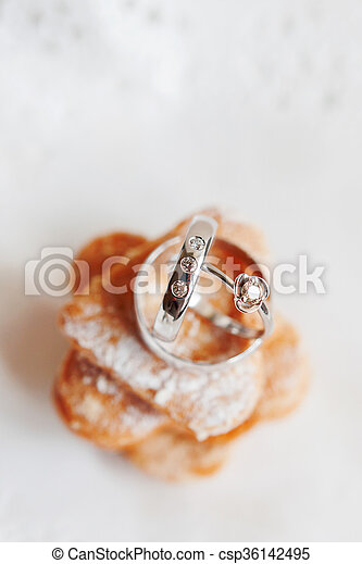 Golden wedding rings with diamonds lie on stack of sweet stock