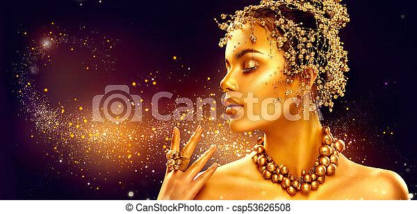 Goldfrauenhaut. Schöne Model-Mädchen mit goldenem Make-up, Haar und Schmuck auf schwarzem Hintergrund - csp53626508