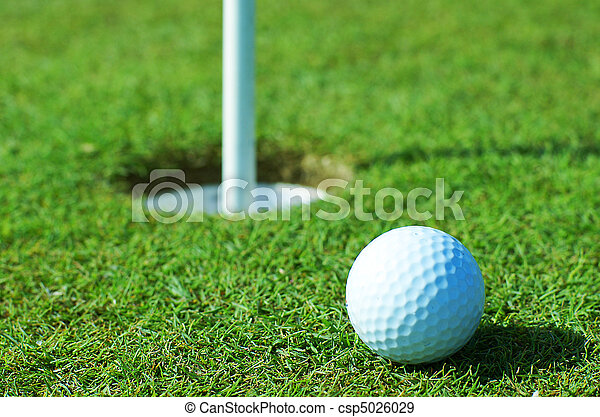 Golf ball on green grass in front of hole - csp5026029