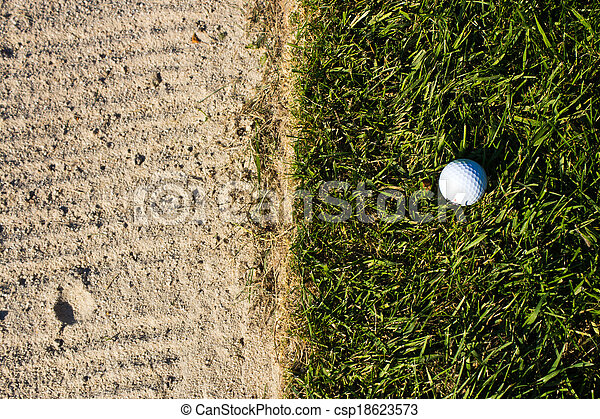 Golf ball on the edge of the sand bunker - csp18623573