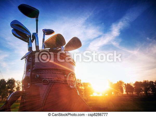Golf gear, clubs at sunset - csp8286777