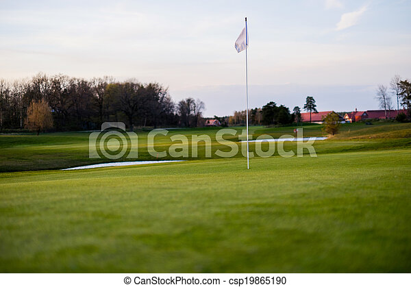 Golf Green with flag with some house in the far distance - csp19865190