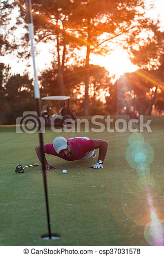 golf player blowing ball in hole with sunset in background - csp37031578