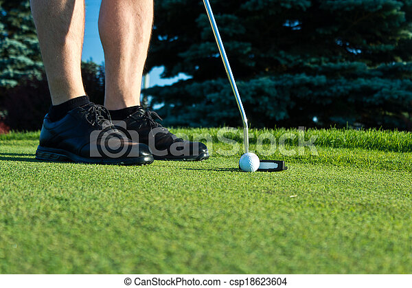 Golf player putting on the green - csp18623604