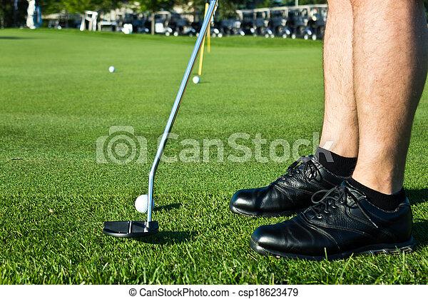 Golf player putting the ball - csp18623479