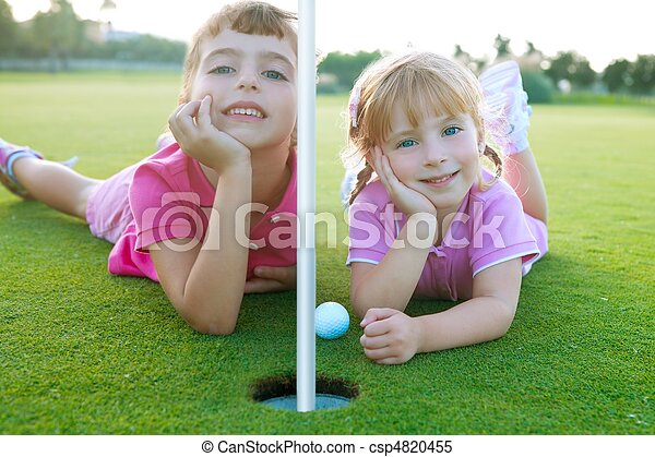 Golf sister girls relaxed laying green hole ball - csp4820455