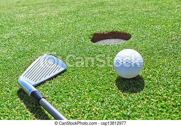 Golf stick and ball on the grass near the hole. - csp13812977